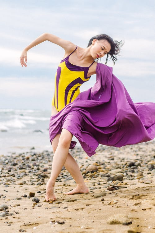 Young slender Asian woman in swimsuit dancing on beach