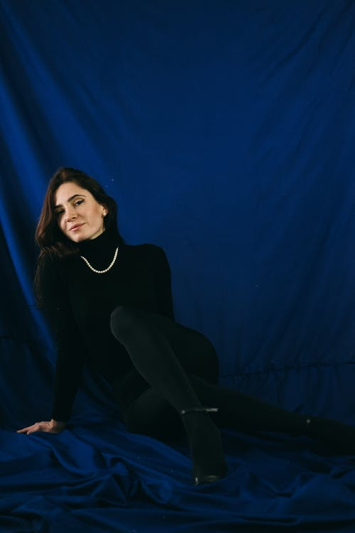 Trendy female with long hair in black outfit looking at camera on blue crumpled textile