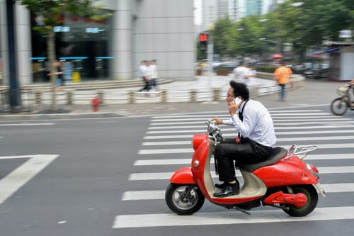 Man in White Long Sleeve Shirt Riding Red Motor Scooter on Road