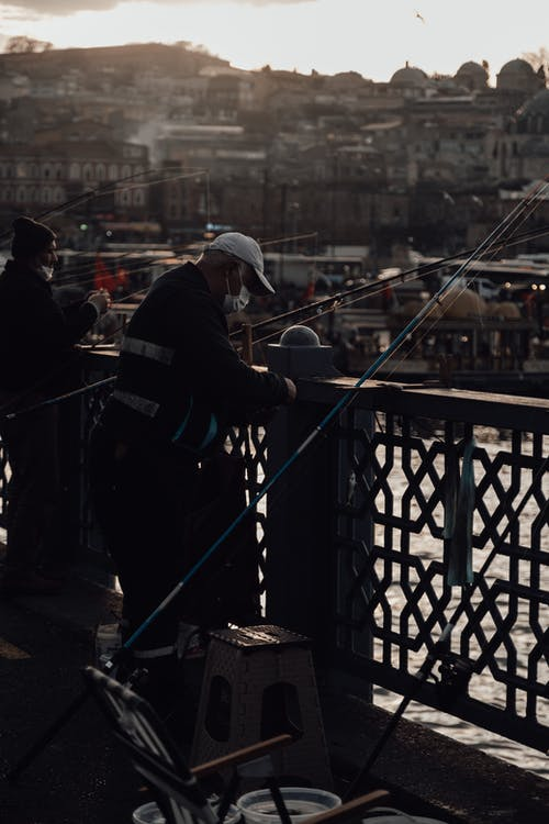 Fishermen in protective masks with fishing rods standing near fence of bridge in old city