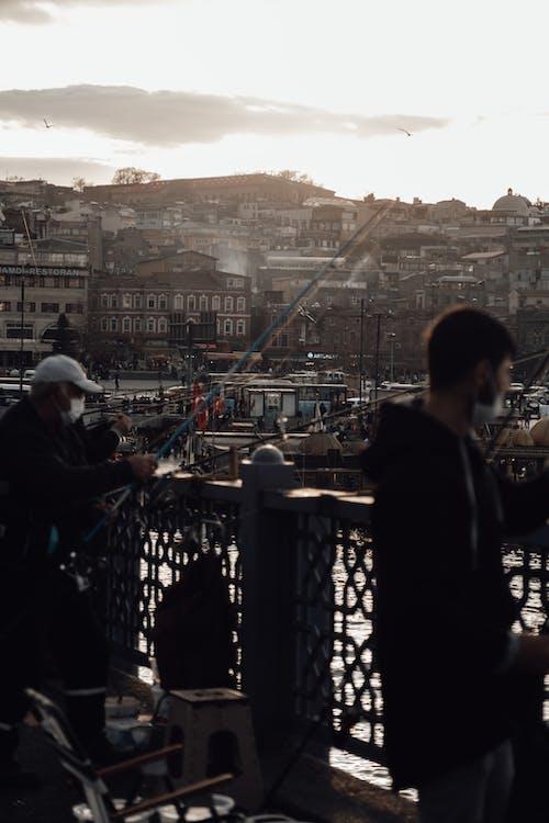 Men in masks standing on bridge and enjoying fishing on bridge over river at sunset