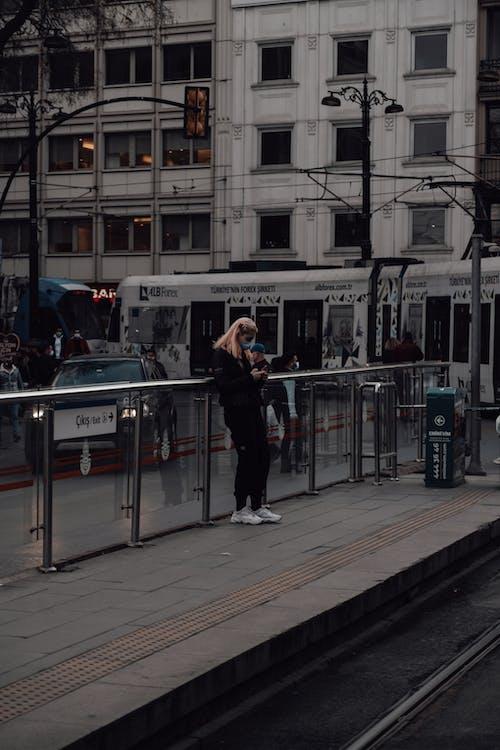 Человек в черной куртке стоит на тротуаре