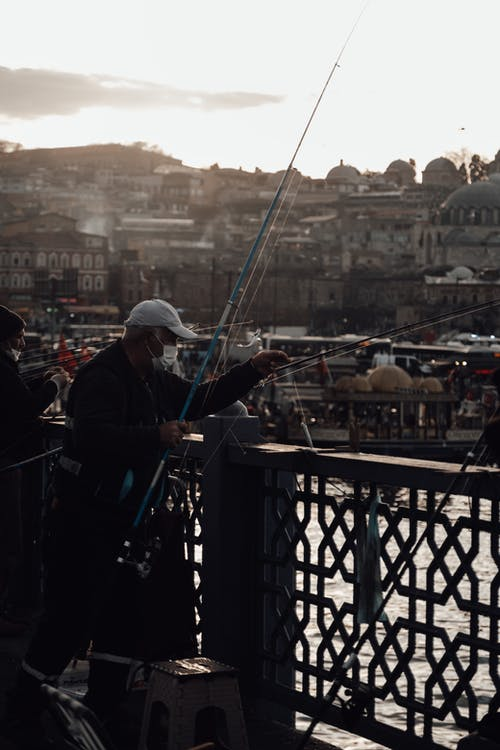 Old fishers catching fish on bridge