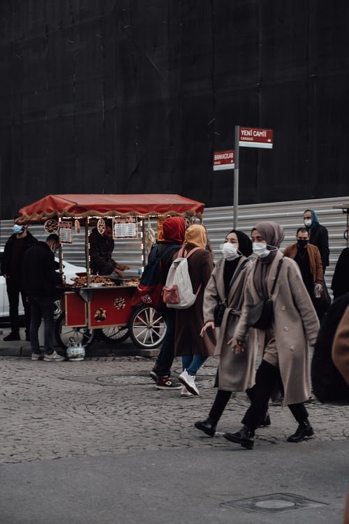 Crowded street with people in masks and warm clothes walking against street food cart