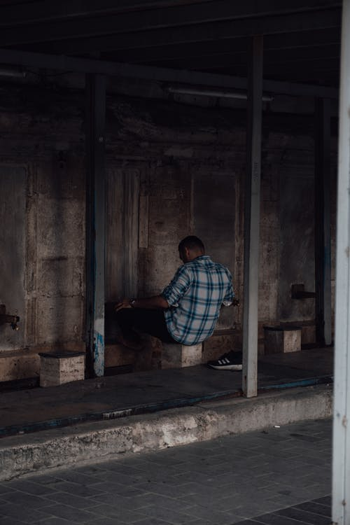 Back view of ethnic male sitting on stone seat and washing legs in washbasin at entrance of old Muslim place of worship