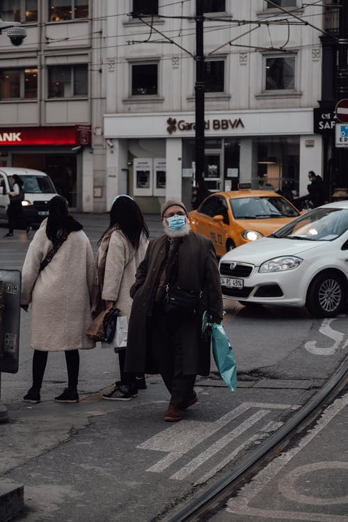 Old man in mask walking on street near pedestrians and automobiles driving on asphalt road during coronavirus pandemic