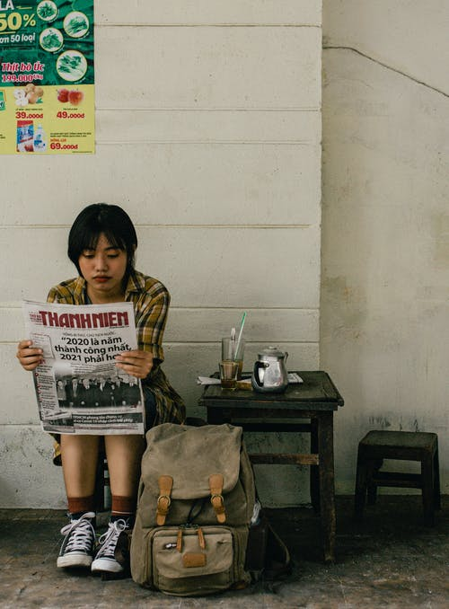 Young woman reading newspaper on street
