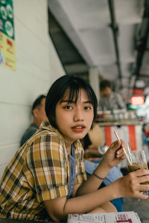 Asian woman with glass of cold beverage