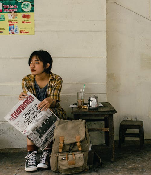 Ethnic female traveler with backpack and newspaper near wall