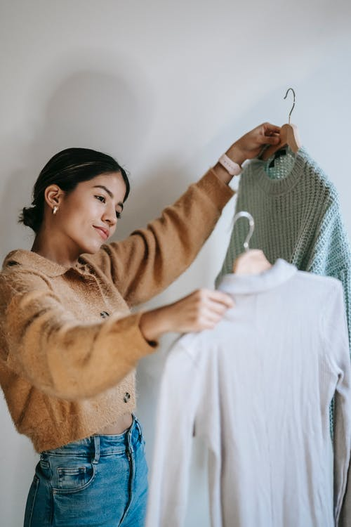 Happy young woman choosing pullovers on hangers