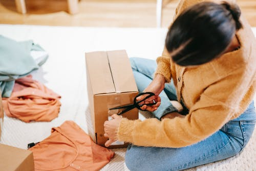 Woman cutting off adhesive tape from box with parcel