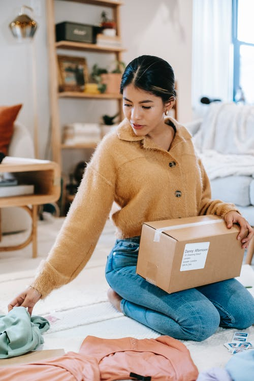 Young female in fashionable outfit with carton box of parcel preparing clothes for sending on blurred background lounge