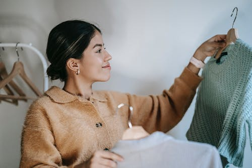 Cheerful young female in stylish cardigan smiling and choosing clothes on hangers in wardrobe