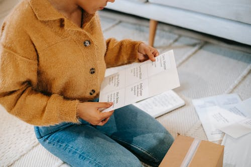 From above of crop anonymous female in trendy soft beige cardigan and jeans reading data on paper