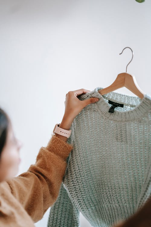 Crop anonymous female designer in casual clothes demonstrating new sweater on hanger while standing in room