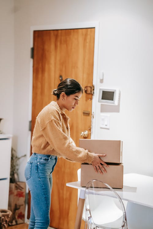 Side view of concentrated female in casual clothes preparing cardboard boxes for delivering