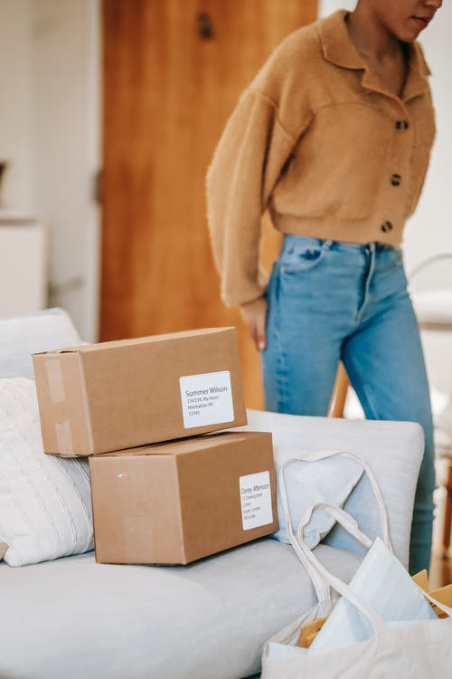 Crop unrecognizable female standing near couch with carton boxes and shopping bag while preparing for delivering