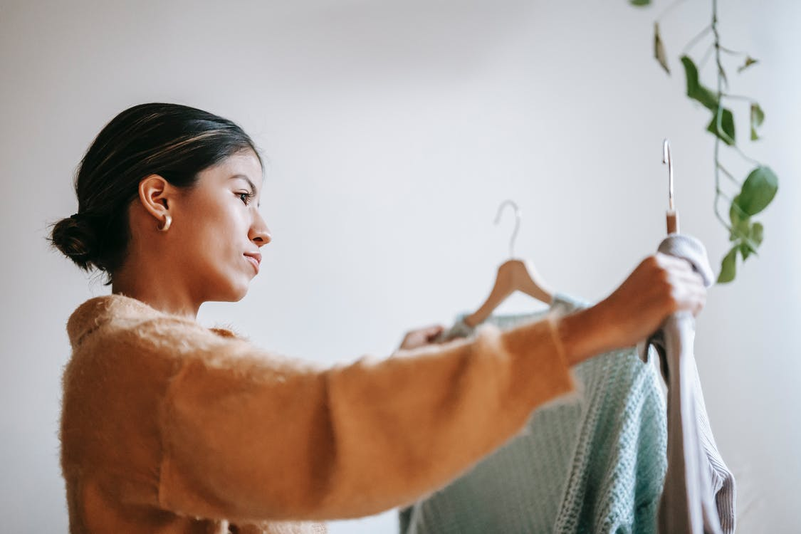 Focused woman choosing clothes at home