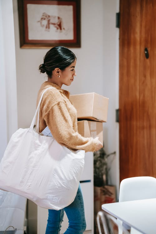 Side view of happy woman carrying cardboard boxes while preparing for delivery service