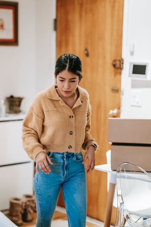 Ethnic woman packing boxes at home