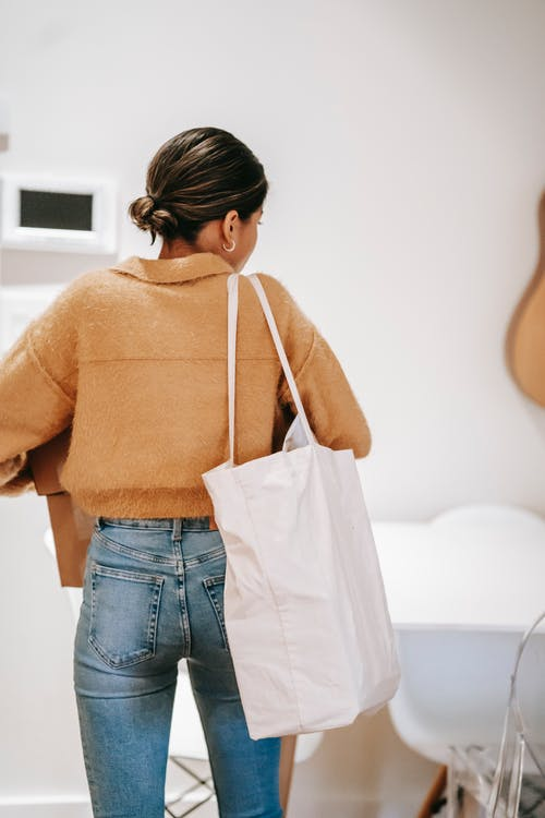 Back view of anonymous dark haired female in casual outfit with huge shopping bag carrying carton boxes