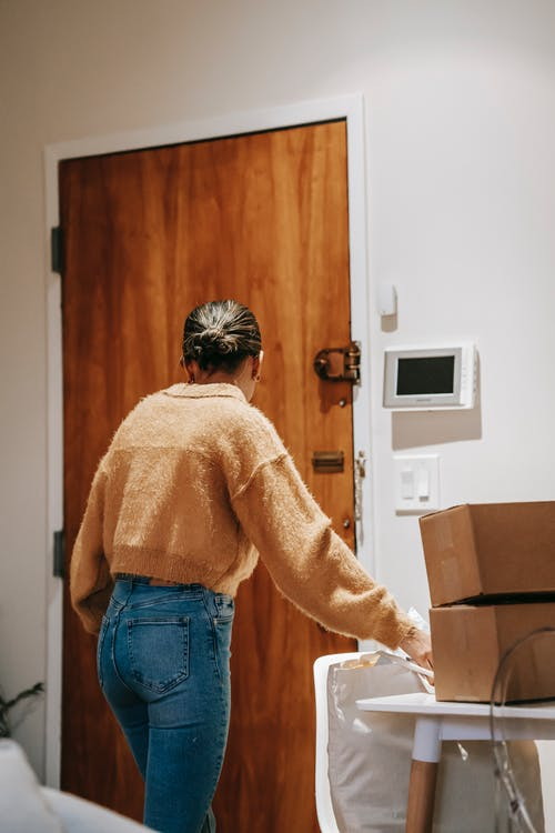 Unrecognizable woman with boxes in apartment