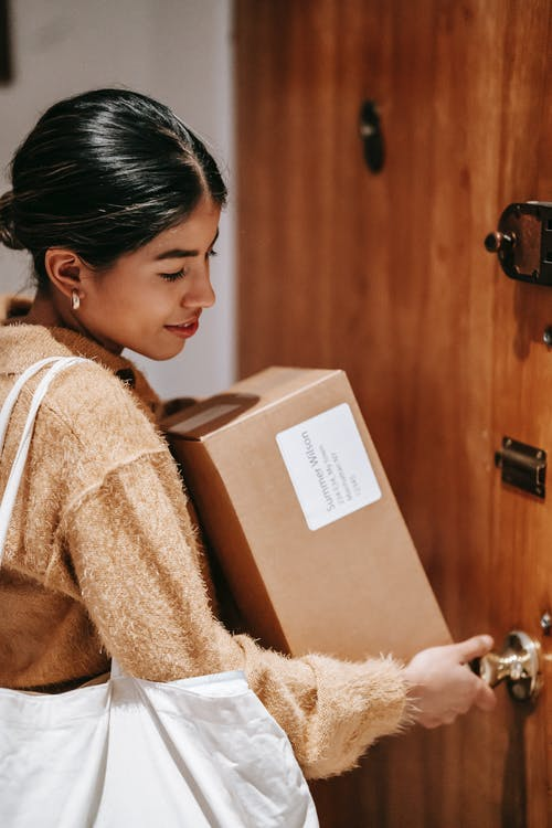 Ethnic woman with carton boxes opening door