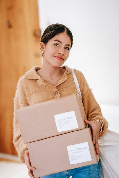 Smiling ethnic woman carrying cardboard parcels