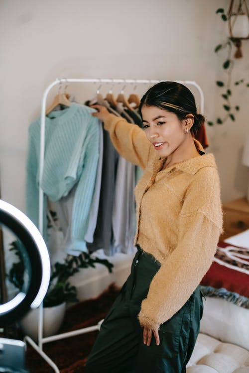 Woman in Beige Sweater and Black Pants Standing in Front of Mirror