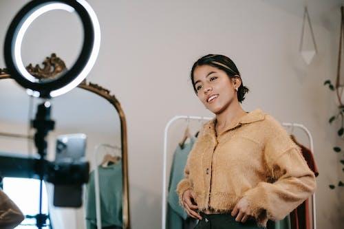 鏡の横に立っている茶色のセーターの女性