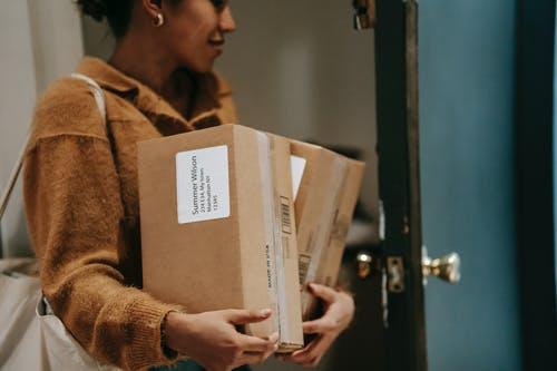 Crop ethnic female walking into open door of apartment with carton boxes with goods from delivery