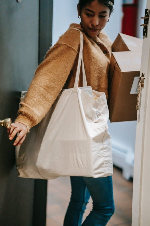 Crop Indian woman in casual clothes with shopping bags and boxes leaving apartment and closing door