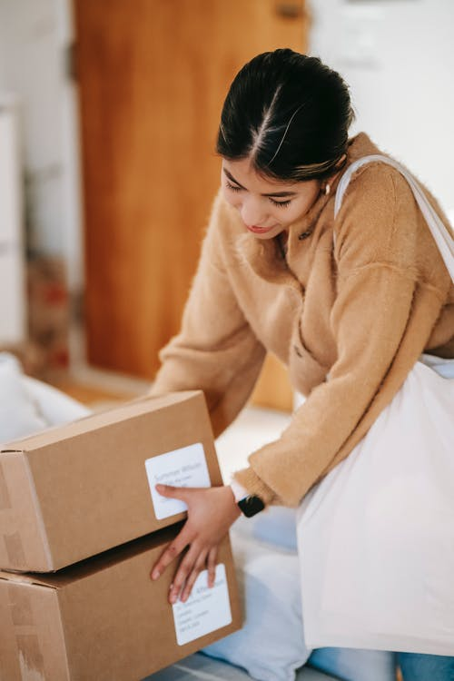 Female customer with shopping bag getting stack of carton boxes with delivered goods at home