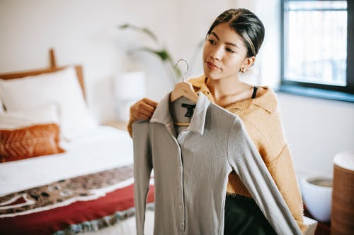 Asian woman trying on clothes in bedroom