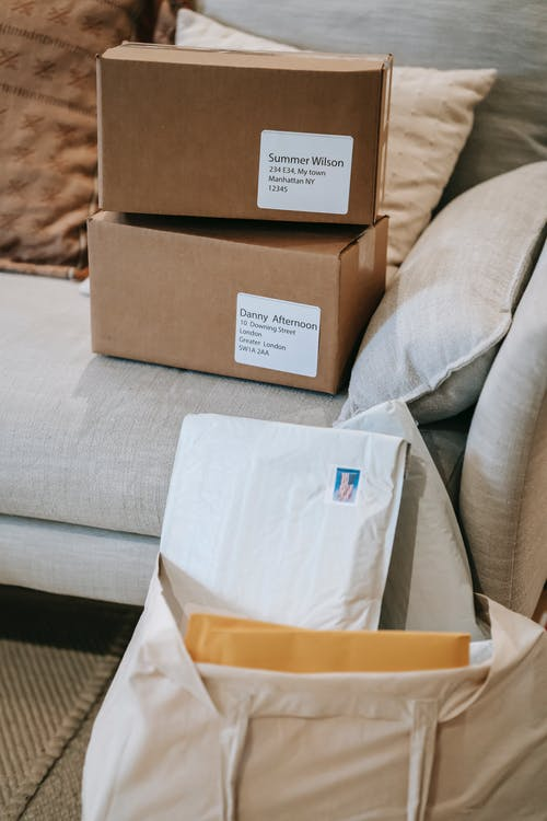 From above of delivered cardboard boxes placed on sofa near letters in envelopes in fabric bag in apartment