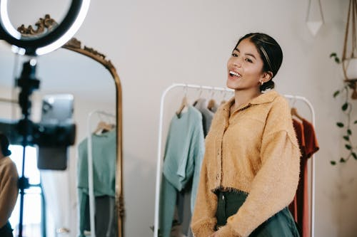 Positive young ethnic female blogger standing in wardrobe and using phone with ring light while filming vlog near mirror and trendy clothes