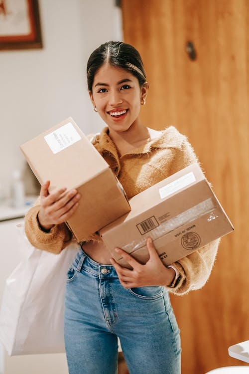 Smiling young ethnic lady in casual outfit standing in light room in house with packages and shopping bag while looking at camera