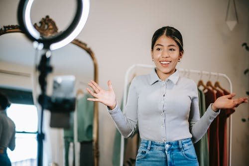 Happy young ethnic female blogger in blouse and jeans standing in wardrobe and using phone with ring light while filming vlog about trendy clothes near mirror