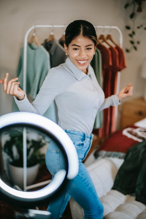 Happy young ethnic female in blouse and jeans standing in room near wardrobe and demonstrating outfit while filming vlog on smartphone on ring light