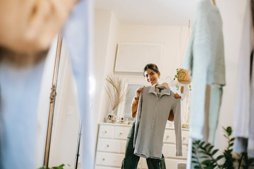Smiling young ethnic woman in casual outfit demonstrating blouse on hanger while selecting clothes and looking in mirror in room near cabinet and wardrobe at bright home