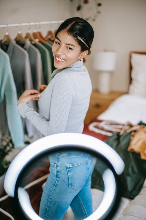 Side view of happy young ethnic female in blouse and jeans standing in room near ring light and clothes on hangers and demonstrating trendy outfit