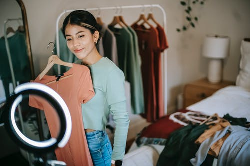 Smiling ethnic woman shooting vlog on phone while demonstrating clothes