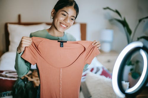 Happy young ethnic female in casual outfit showing pink dress while selecting clothes near ring lamp and bed near potted plant while standing in light room at home