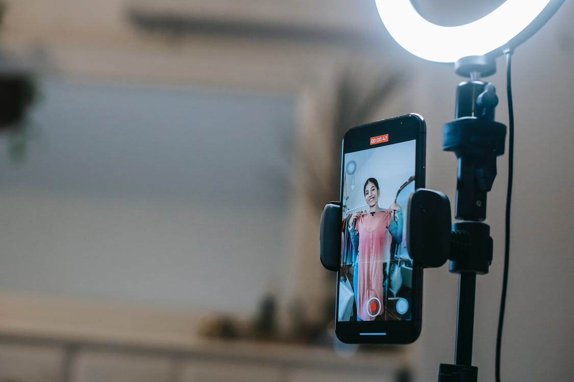 Faceless lady filming video on mobile while demonstrating dress