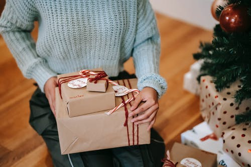 Crop unrecognizable female with heap of gift boxes sitting on floor during New Year holiday at home