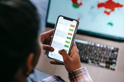 Crop broker using trading app on smartphone against laptop