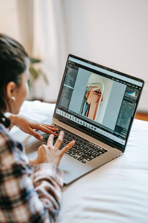 Crop ethnic freelancer retouching photo on laptop in bedroom