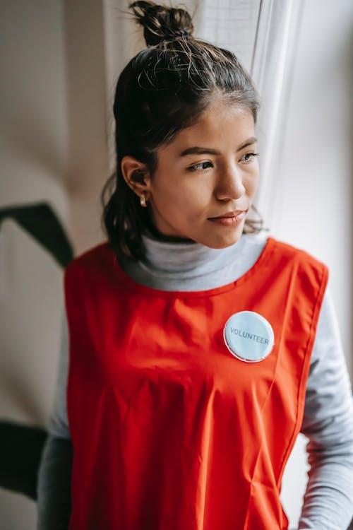 Ethnic volunteer woman in light room