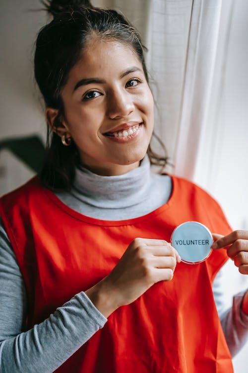 Cheerful volunteer woman in red uniform