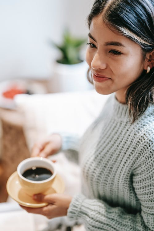 From above of crop smiling ethnic lady with short dark hair in warm knitted sweater standing with cup of coffee and saucer and looking away in light living room